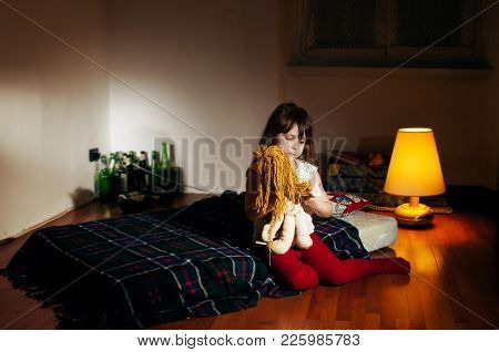 Lonely Caucasian Girlie In The Empty Dark Room Holding A Doll, Bottles In Background