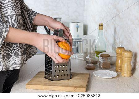 Grating Orange Zest. Female Hands Use Grater To Make Peel In Kitchen Environment