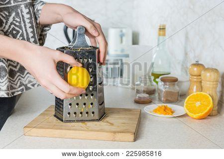 Grating Citron Zest. Female Hands Use Grater To Make Lemon Peel In Kitchen Environment