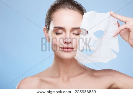 Woman Removing Mask From Face