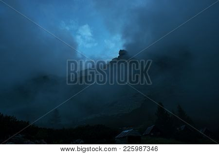 Heavy Clouds Or Haze Over A Distant Mountain Peak.