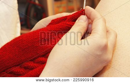 Woman Knits With Knitting Needles Red Sweater From Natural Woolen Threads
