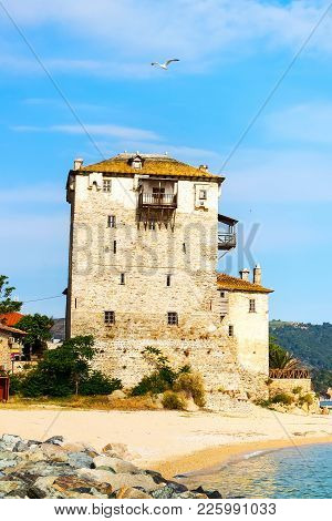 Ancient Ouranoupolis Tower On Athos Peninsula In Halkidiki, Greece, Pier, Sea Shore And Aegean Sea W
