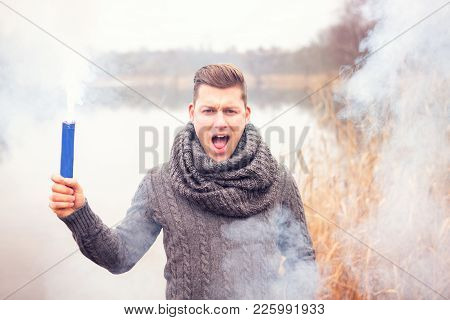 Handsome Man In Front Of Lake Holding A Smoking Torch
