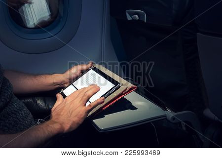 Young Man Using His Tablet On A Plane During A Flight.
