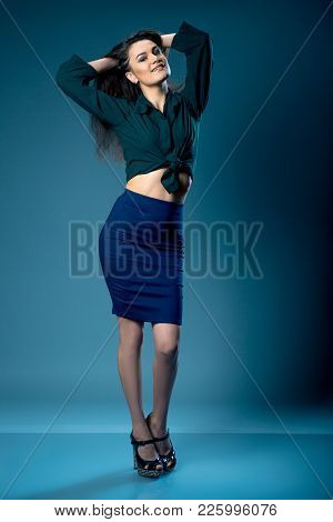 Portrait Of Young Gorgeous Dark-haired Girl With Provocative Make Up Wearing High Waisted Blue Skirt