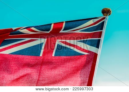 The Uk Red Ensign The British Maritime Flag Flown From Yacht Sail Boat, Blue Sky. Summer And Travel