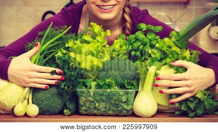 Woman Young Positive Housewife In Kitchen With Many Green Leafy Vegetables, Fresh Produce Organicall