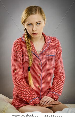 Adolescence Problems Concept. Sad Young Teenager Woman Sitting On Bed Feeling Depressed.