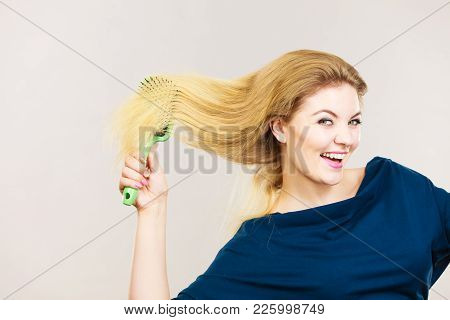 Woman Brushing Her Long Blonde Hair Using Brush, Morning Beauty Routine. Haircare And Hairstyling Co