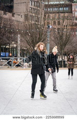 Stockholm, Sweden - February 3, 2018: Front View Of A Young Couple Skating At A Public Ice Skating R