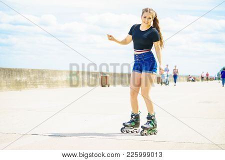 Happy Joyful Young Woman Wearing Roller Skates Relaxing After Long Ride. Female Being Sporty Having