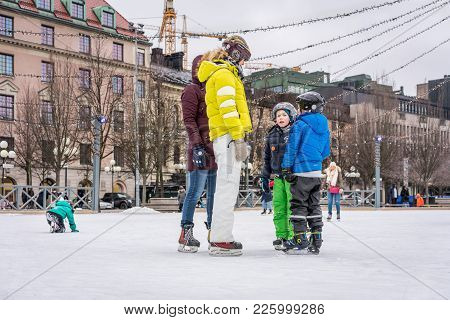 Stockholm, Sweden - February 3, 2018: Side View Of Two Woman And Children Skating At A Public Ice Sk