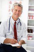 Senior doctor writing prescription poster