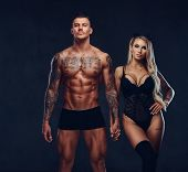Beautiful couple, handsome tattooed male and alluring girl in black underwear holding hands, posing in studio. poster