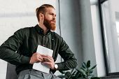bearded businessman holding tablet and looking away poster
