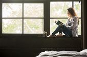 Pensive dreamy girl holding book sitting on sill at home looking at big window dreaming, thoughtful young woman thinking of reading new novel relaxing in modern cozy loft bedroom alone poster