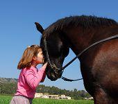little girl a black stallion in a field poster