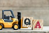 Toy yellow forklift hold letter block Q to complete word QA (Abbreviation of Quality Assurance or Frequently asked question)on wood background poster