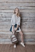 Smiling girl wearing natural makeup, linen dress and boots. Concept of purity, youth, beautiful skin  posing on pastel wood background, holding a silver backpack in hands. poster