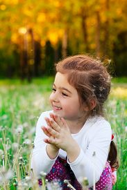 Beautiful little child smiling with dandelion flower in summer park at sunset
