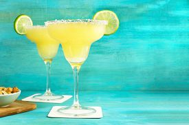 A Photo Of Lemon Margarita Cocktails With Wedges Of Lime And A Salted Nuts Snack, Retro Styled, With