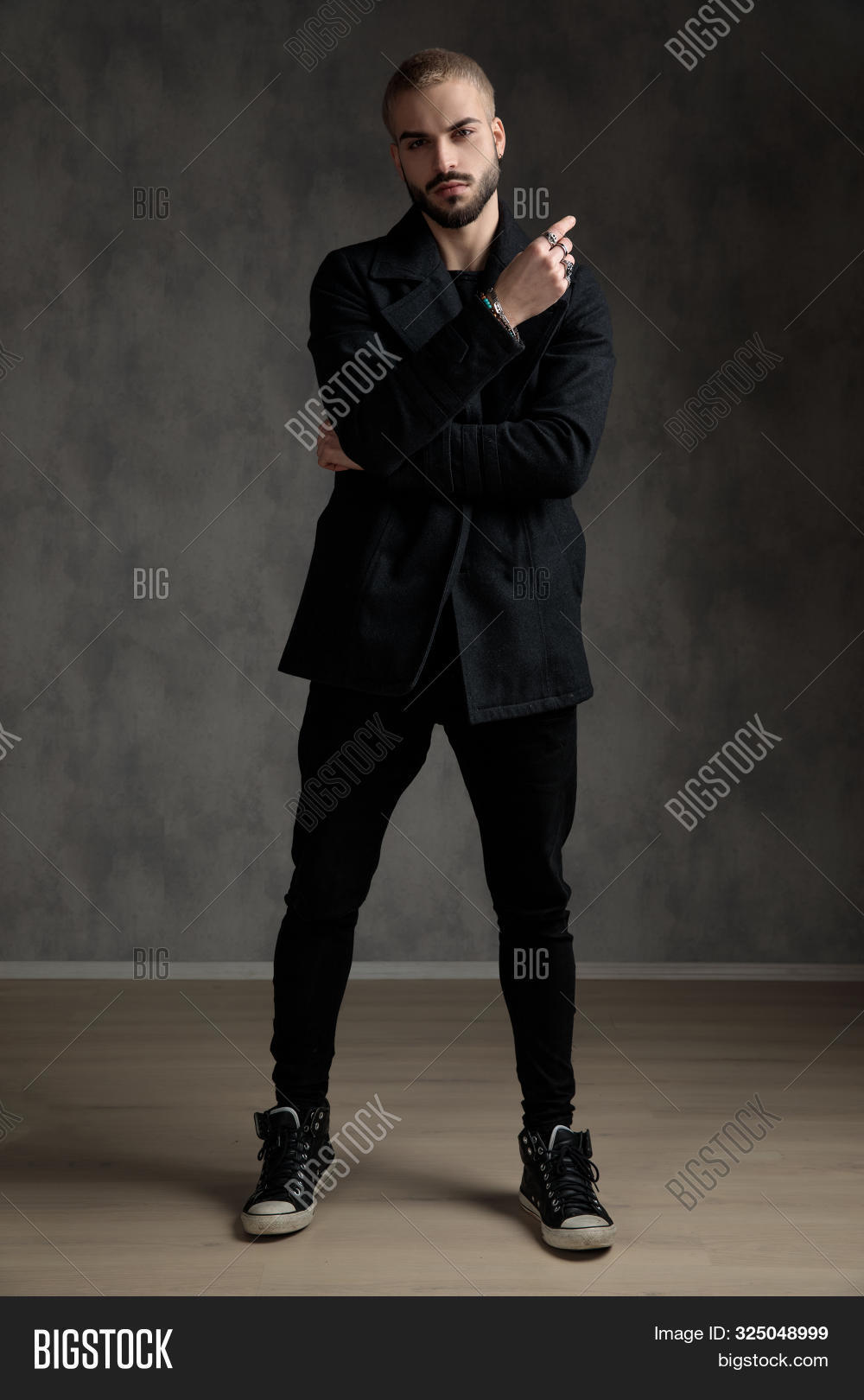 casual fashion model wearing longcoat, holding hands and standing on grey background in studio, full body