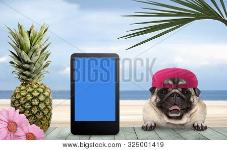 Smiling Tropical Summer Pug Dog With Cap And Tablet, With Paws On Vintage Green Wooden Table And Sea