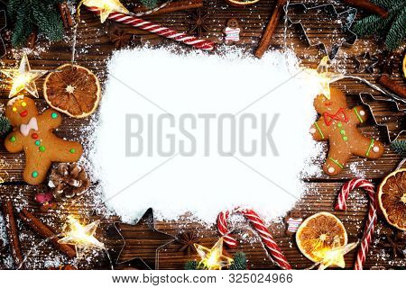Christmas food frame. Gingerbread cookies, spices and decorations on wooden background with copy space on snow