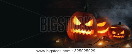 Halloween pumpkin heads jack o lantern and candles in fog on wooden background