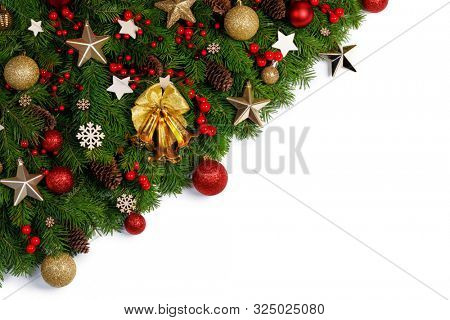 Christmas Border frame of tree branches on white background with copy space isolated, red and golden decor, berries, stars