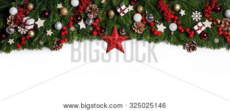 Christmas Border frame of tree branches on white background with copy space isolated, red and golden decor, berries, stars, cones