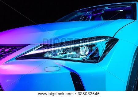 Close-up Headlight Of A White Expensive Crossover Under A Bare And Pink Neon Light. Exterior Detail.