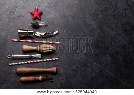 Cocktail utensils christmas tree. Set of bar tools on stone table. Top view flat lay with copy space