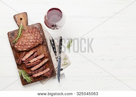Grilled beef steak on wooden board and red wine. Top view flat lay with copy space