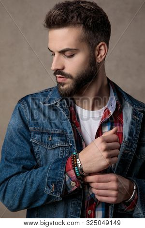 casual young fashion man wearing blue denim jacket, adjusting bracelets and looking down side, on brown background in studio
