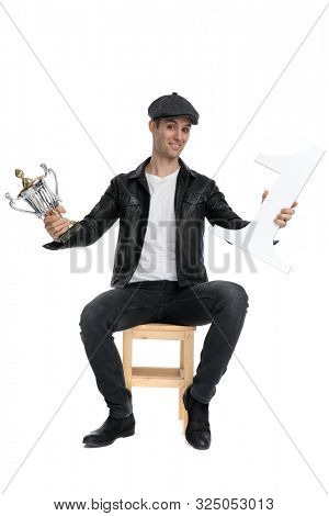 attractive casual man wearing a black leather jacket and hat sitting and presenting his number one and cup cocky against white studio background