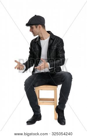 young casual man wearing a black leather jacket and hat sitting while talking and looking to a side intrigued against white studio background