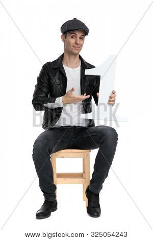 beautiful casual man wearing a black leather jacket and hat sitting and presenting his number one cocky against white studio background