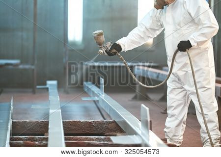 industrial painter in chamber painting metal detail