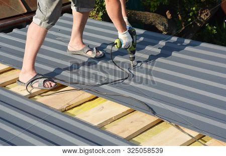 Roofing Construction. Roofer With Crew Gun Installing  Lightweight Metal Roof Tiles Roofing  Constru