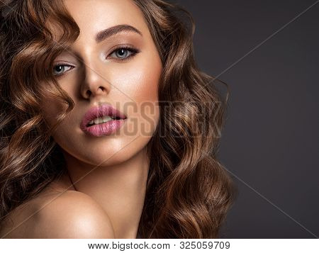 Beautiful woman with brown hair. Beautiful face of an attractive model with fashion makeup. Woman with beauty long curly  hair. Closeup portrait of a caucasian female. Stunning girl.