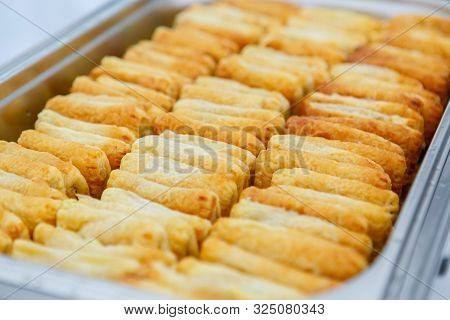 A Closeup Of Fresh Puff Pastry Buns In The Metal Container