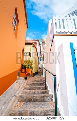 Beautiful narrow cobbled street in Jardim do Mar, Madeira Island, Portugal. Stone staircase along with colorful buildings. Orange and white facade. Mediterranean style. Summer vacation destination poster
