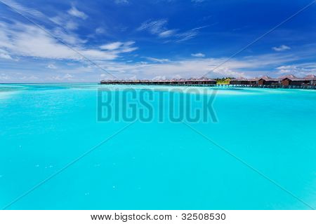 Overwater villas in tropical blue laggon of Maldives