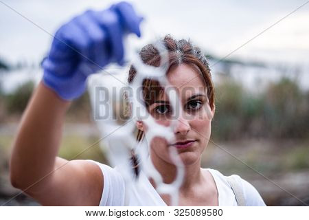 Stock Photo Of A Detail Of The Face Of A Girl Looking At The Camera Who Shows Us A Piece Of Plastic