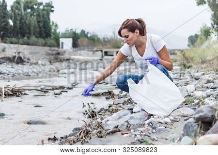 Stock Photo Of A Girl With Blue Gloves Crouched On The Bank Of The River Collecting Pieces Of . Recy