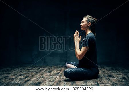 Rear View Of Young Woman Practicing Yoga Sitting In Lotus Pose With Namaste In Dark Room And Copy Sp