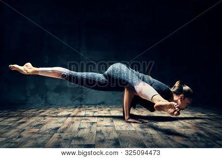 Young Woman Practicing Yoga Doing Hurdler Pose In Dark Room. Eka Pada Koundinyasana. Healthy, Wellne