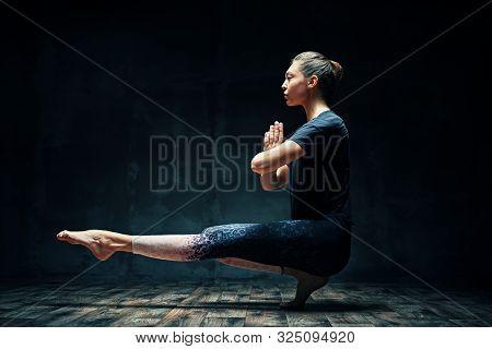 Young Beautiful Woman Doing Yoga Asana Tiptoe Pose Prapadasana Variation On Dark Room. Practicing Yo